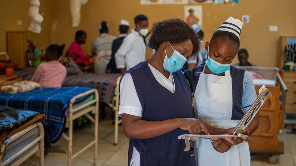 Healthcare workers reading a chart at Mwandi Mission Hospital in Zambia in May 2021.