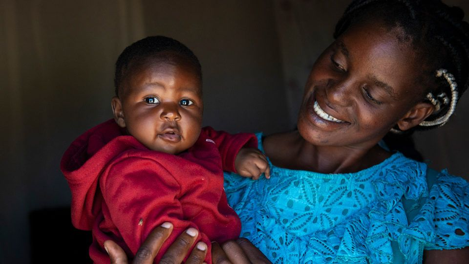A mother holding her smiling baby girl in Zambia in May 2021.