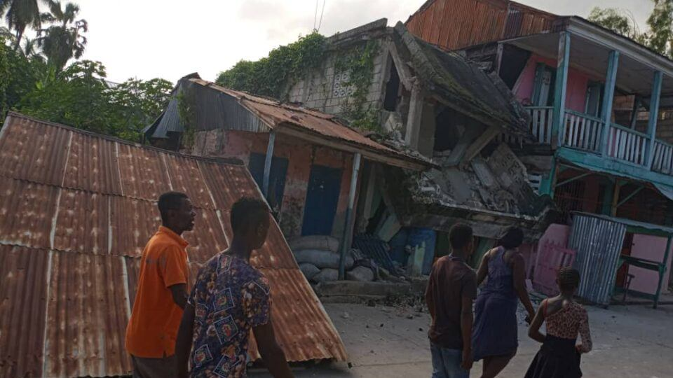 people walking near collapsed buildings after earthquake in haiti