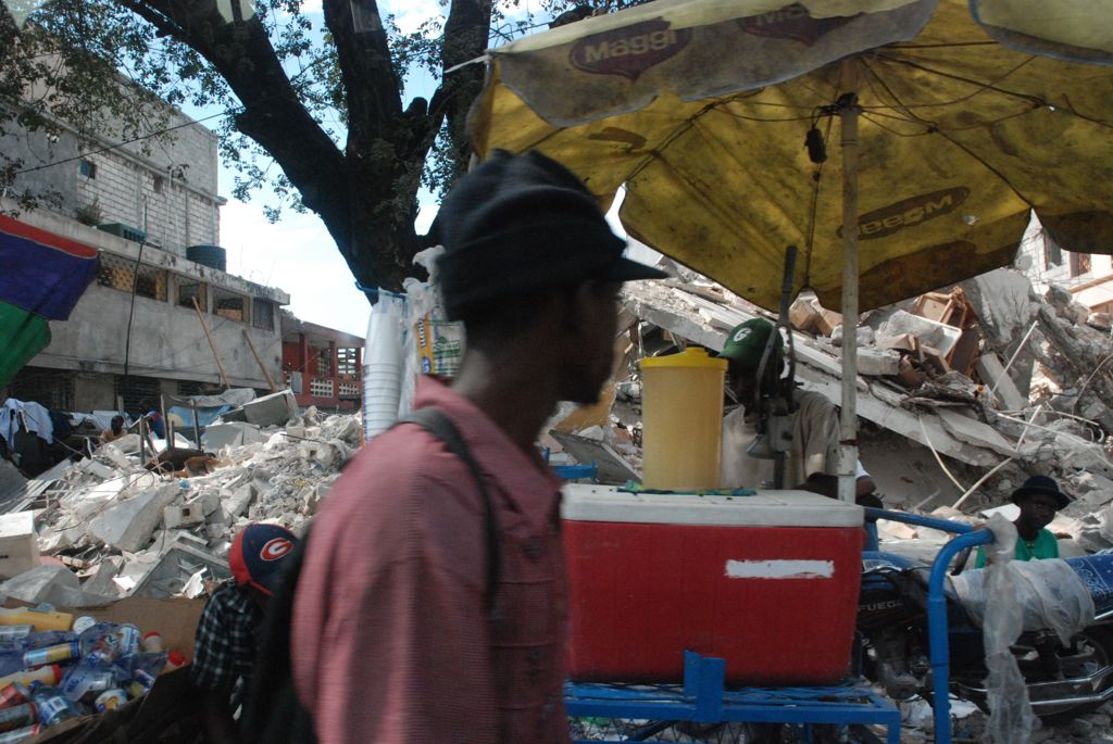 a man looks at the destruction following earthquake on saturday