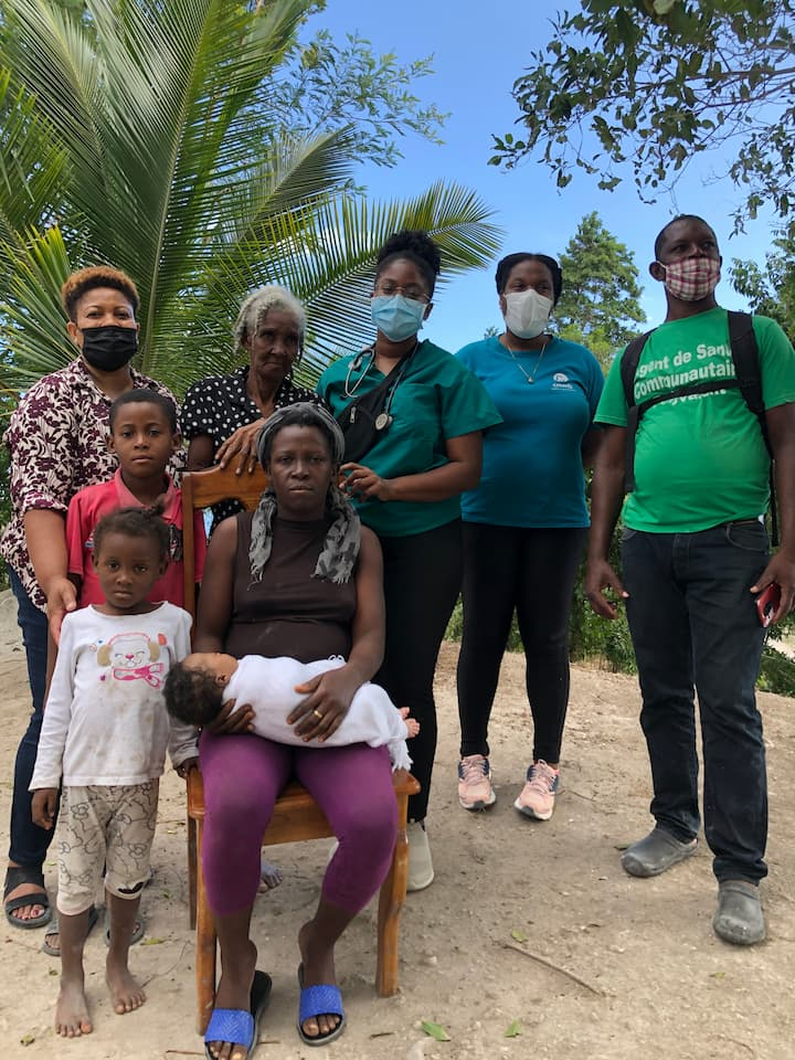 family stands in front of house with volunteers