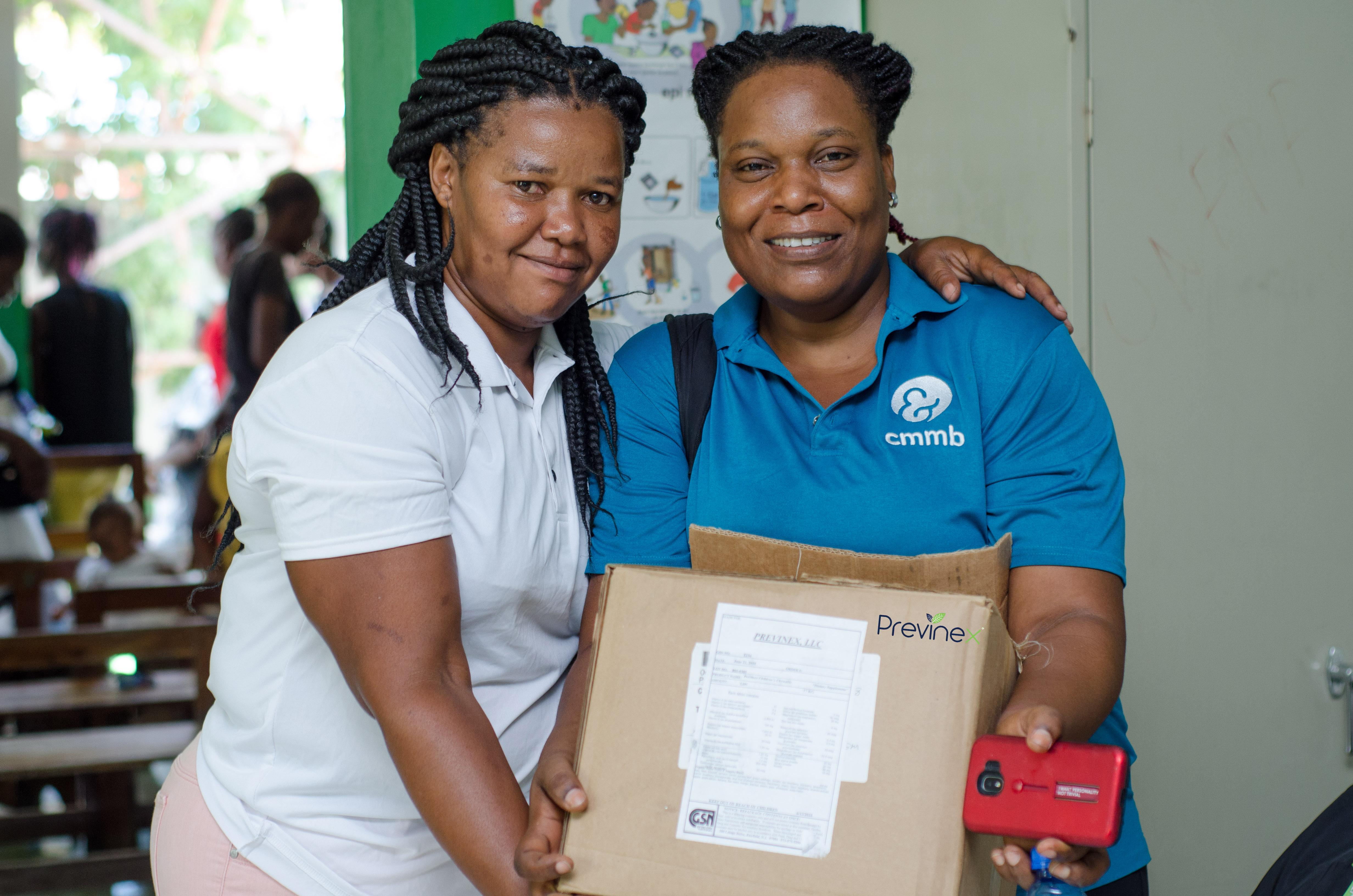 two nurses in haiti hold box with previnex vitamins