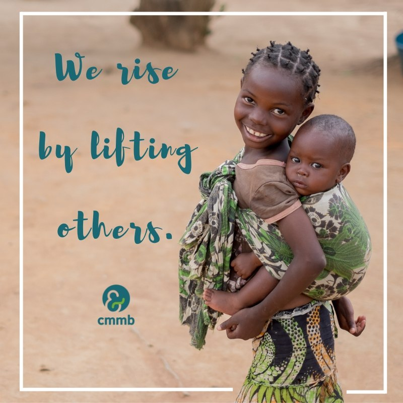 Girl holding brother from Zambia. Quote: We rise by lifting others.
