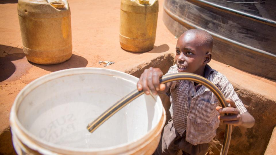 boy fills container with water in Kenya