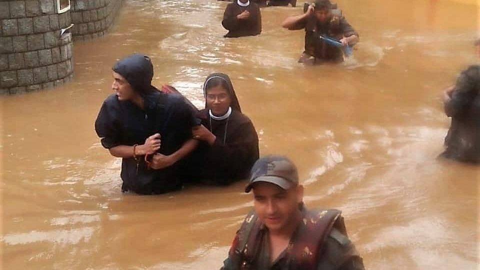 Sisters are assisted through the flood.